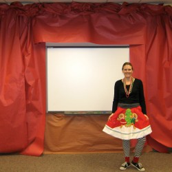 teacher in Christmas outfit standing in front of a stage