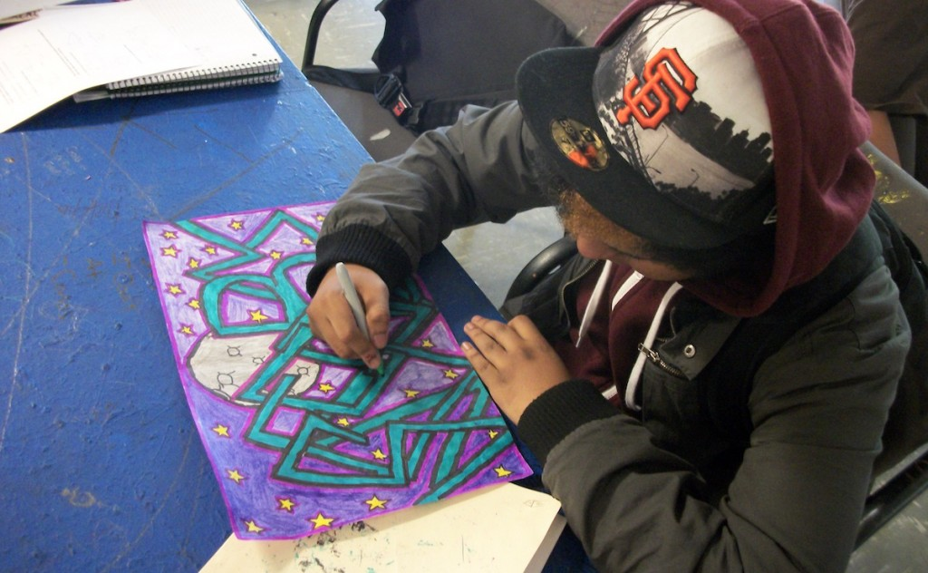 student working on graffiti piece