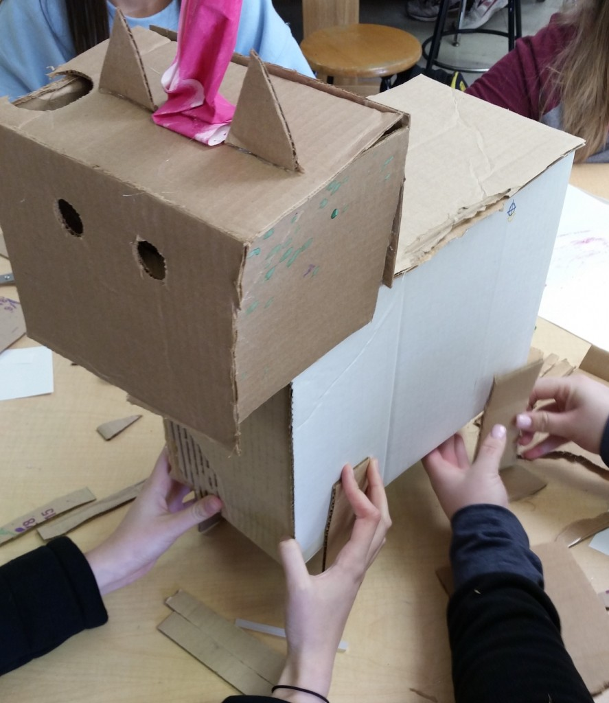 students collaborating on cardboard sculpture