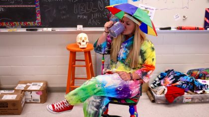 author dressed in tie-dye coveralls with umbrella on head