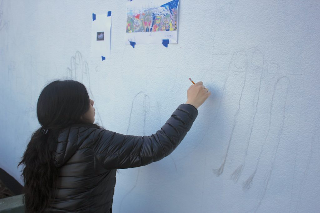 student drawing large on a wall