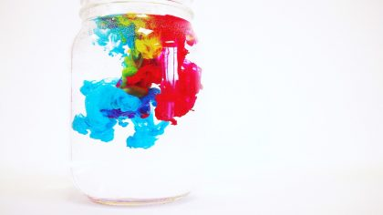colors mixing in water in a jar