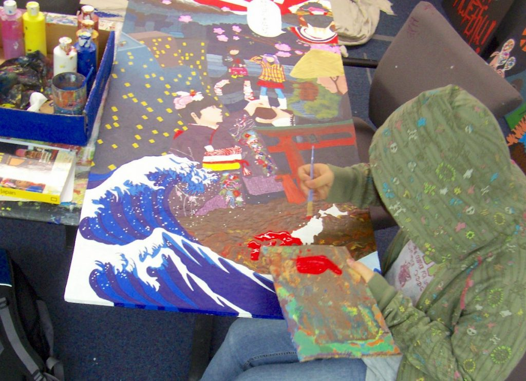 student working on large, detailed painting