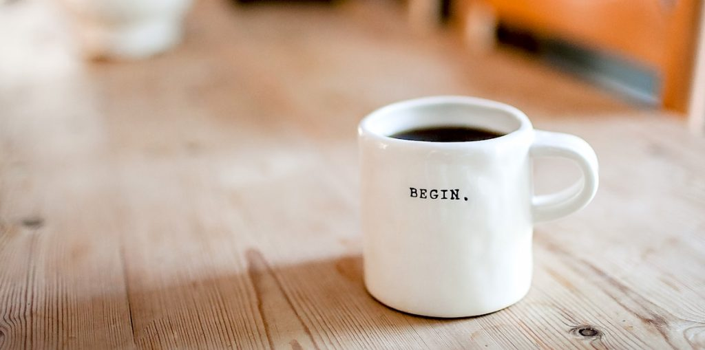 "coffee cup that says ""begin"""