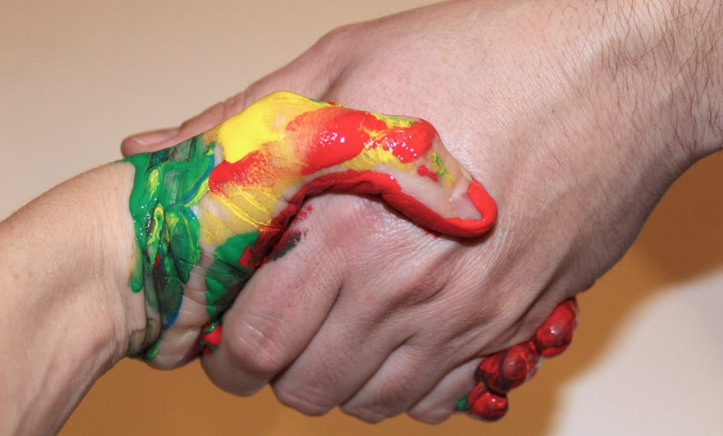 handshake where one hand is painted
