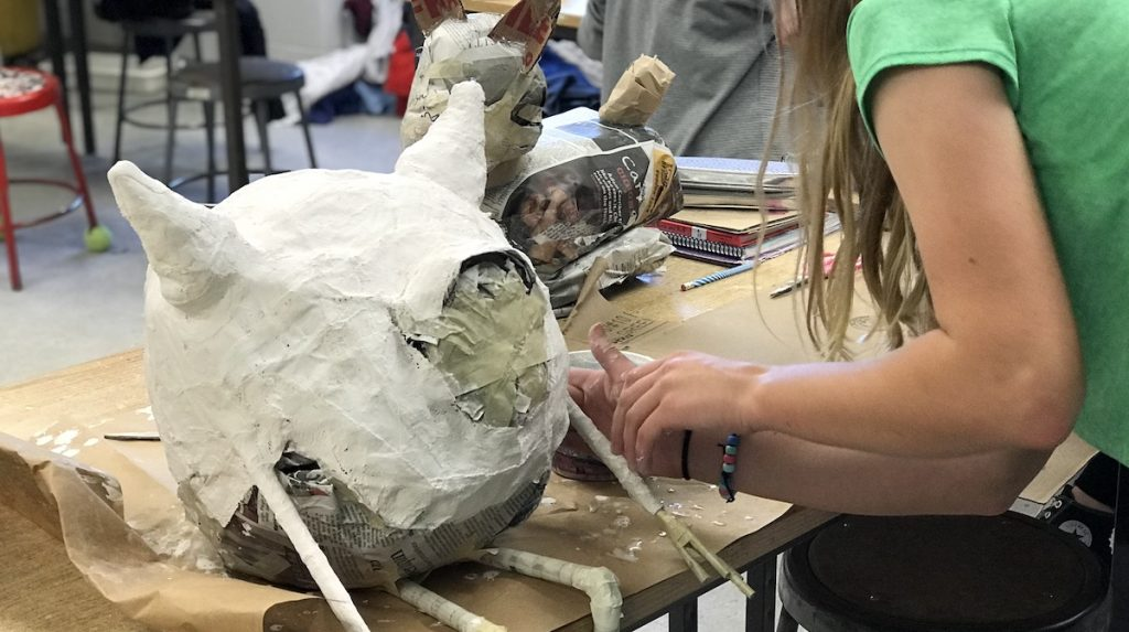 student covering sculpture in gauze