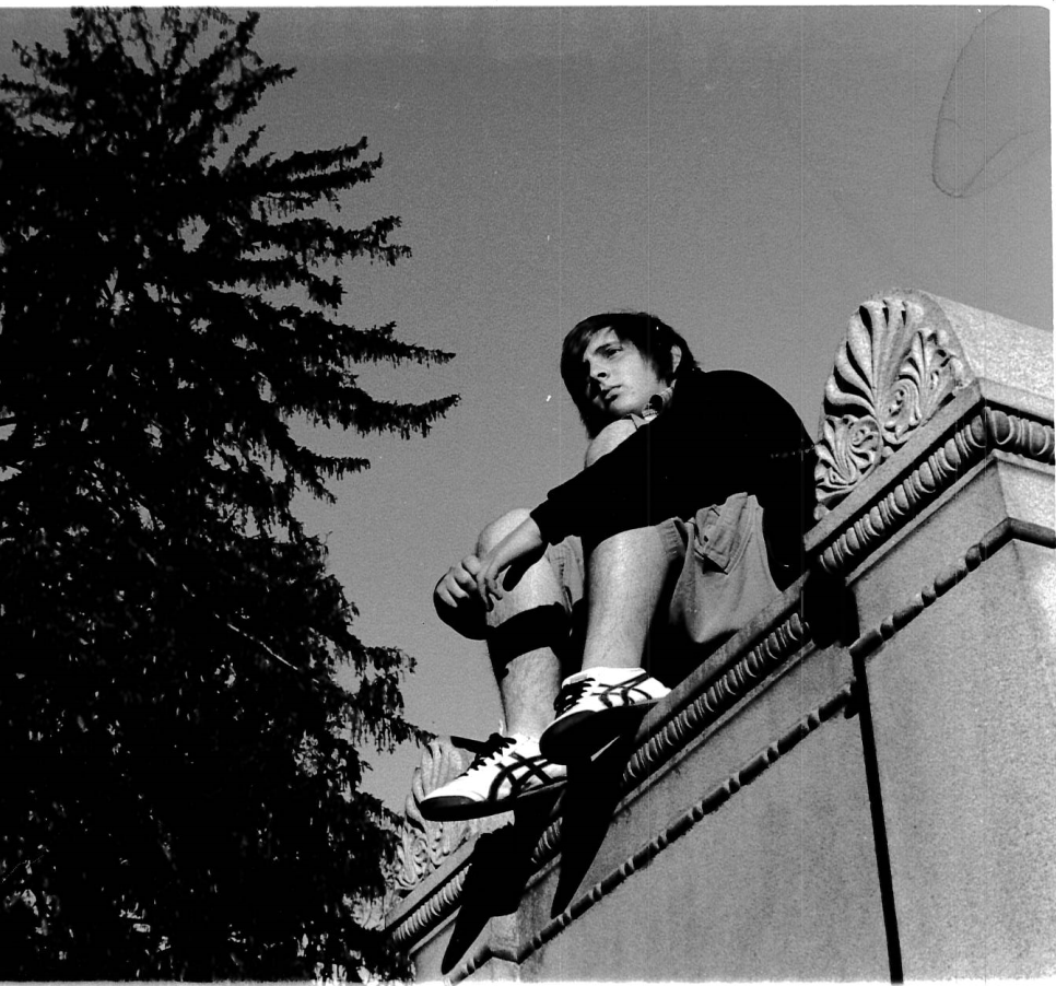 black and white photo of student sitting on a ledge