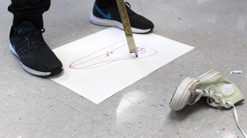 student drawing with a meter stick