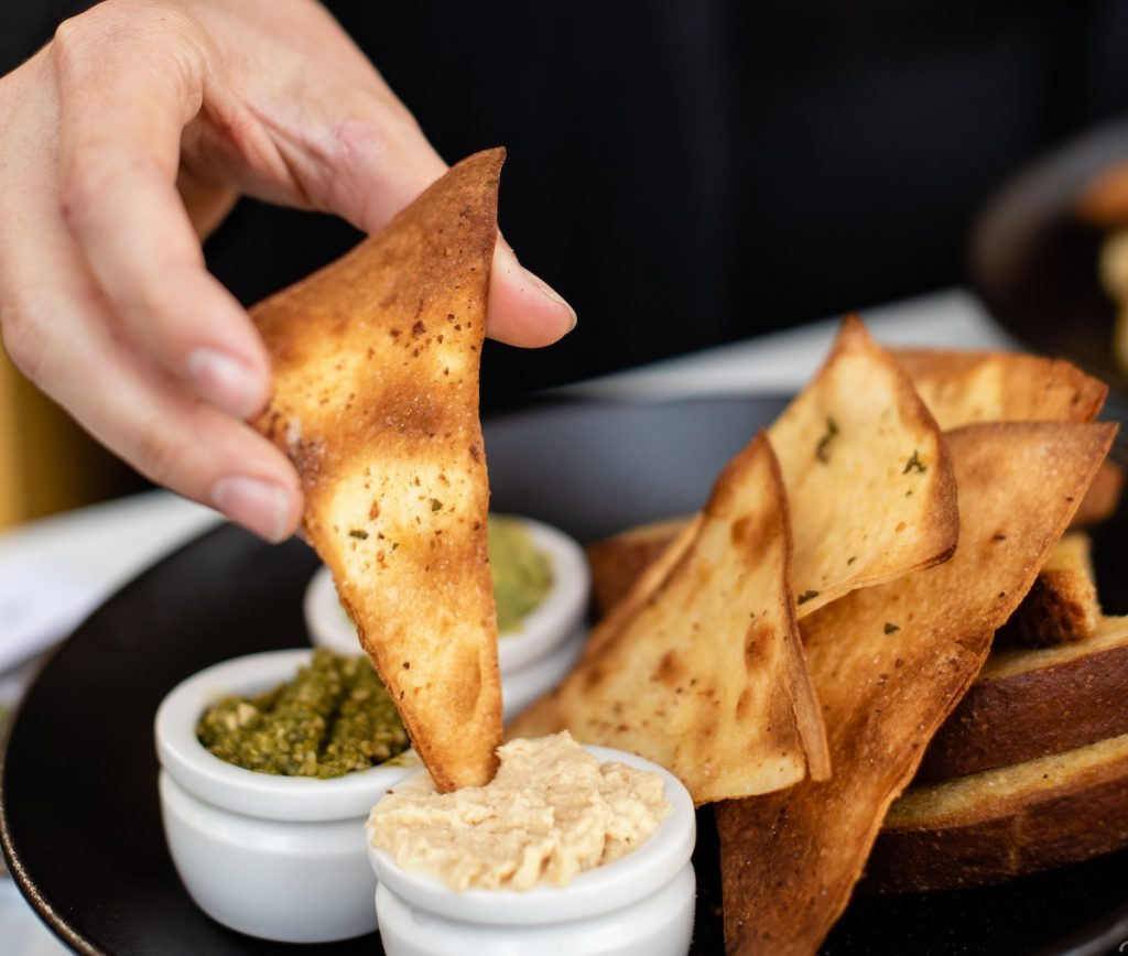 person dipping pita chip into dip