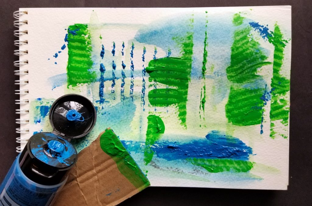 blue paint tube with painting and cardboard