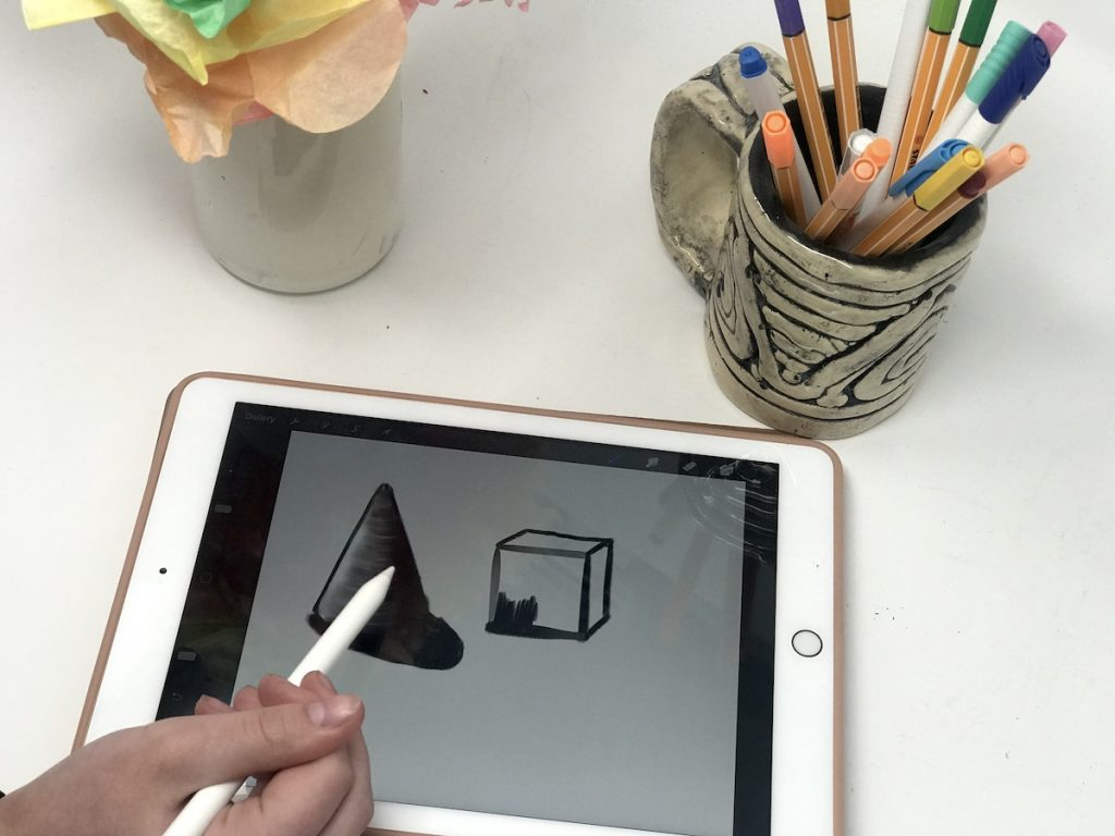 image of artist drawing a cone and cube digitally on an ipad