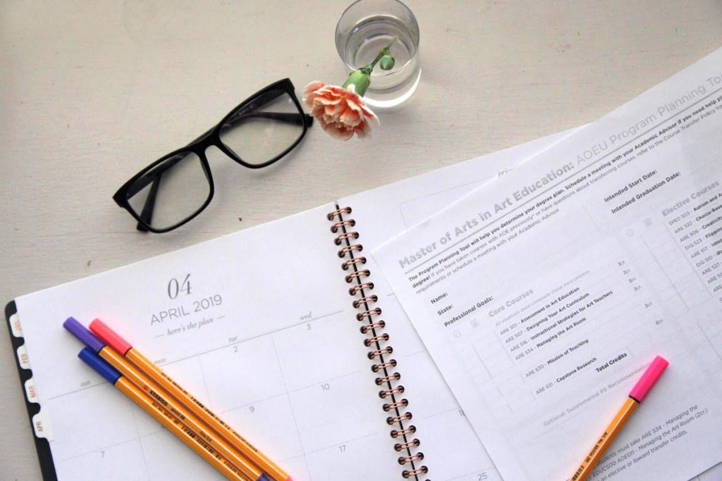 calendar, planning sheet, and glasses on desk