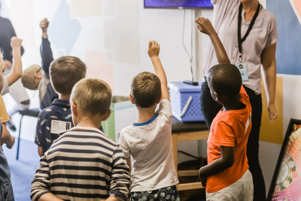Image of students raising hands in a classroom