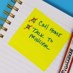 Image of a post-it note with call home and talk to principal