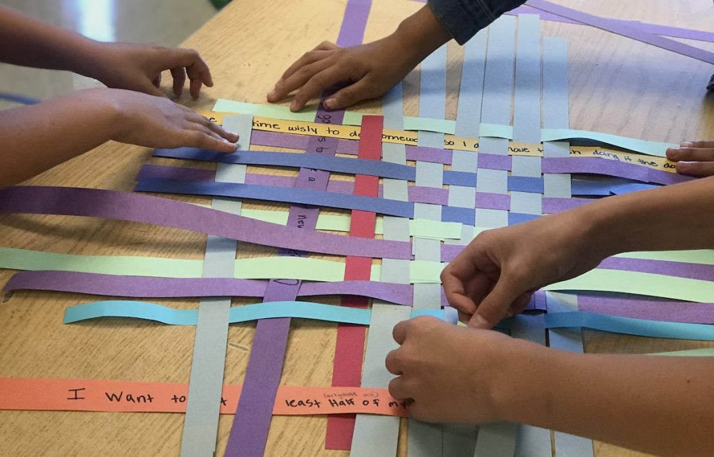 students weaving paper together