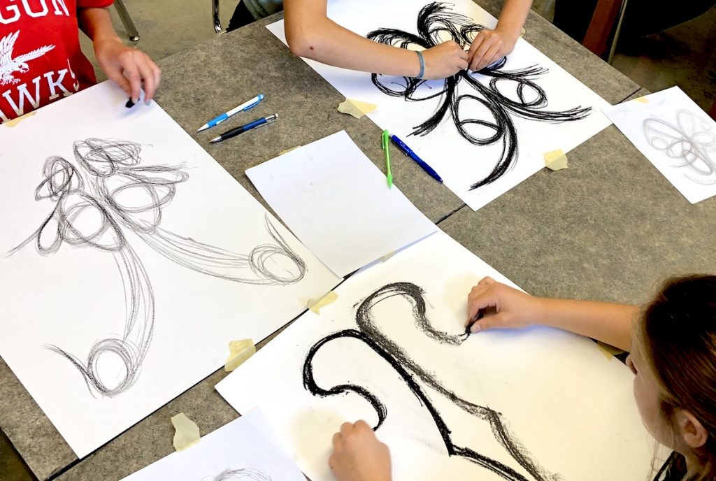 Students doing symmetrical charcoal drawings