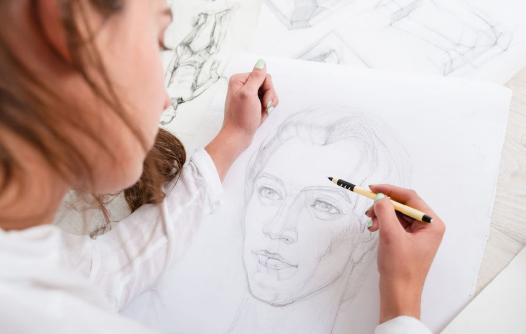Artist drawing pencil portrait close-up