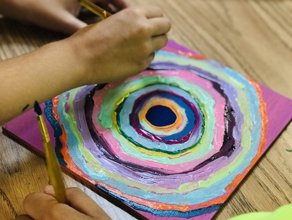 "students painting artwork in the style of ""the dot"""