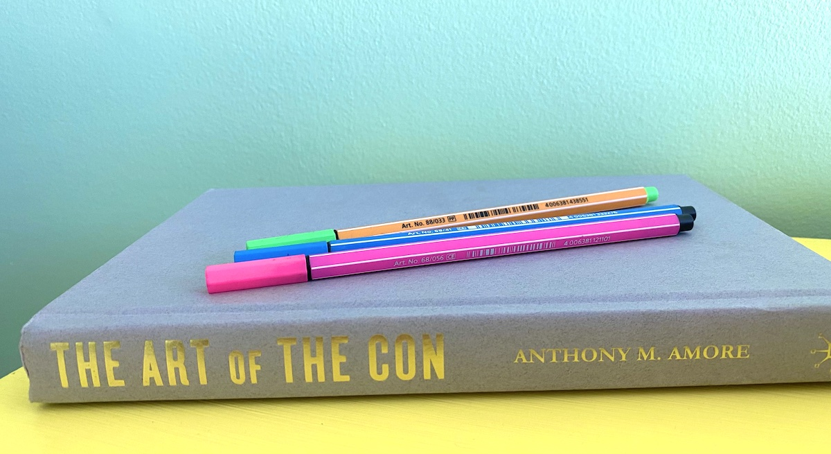 the book 'the art of the con' and pens