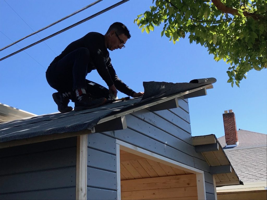 man on roof of a shed
